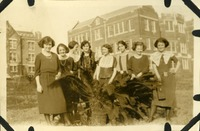 Eight Women Standing Behind a Plant
