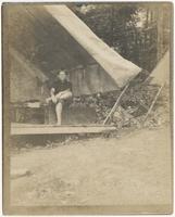 Child sitting on trunk under tent