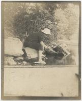 Child sitting on riverbank, looking into the water