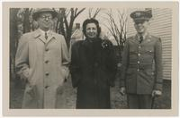 Woman and two men, one in uniform, posing in front of house
