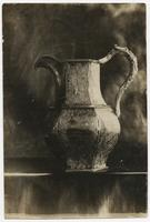 An intricate pitcher with inscriptions and engravings