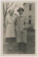 A couple posing together in front of a house