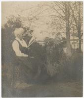 Woman of the Eppes family reading in a chair in the yard of the plantation