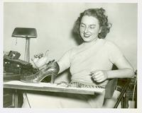 Rosalie Sutton at desk playing with baby alligators and an alligator-skin shoe