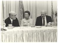 Coral Gables, Florida. Margit Dirac at head table speaking to two unidentified men