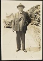 Charles Dirac pausing for a photo on a sidewalk