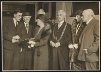 Charles and Florence Dirac with others beside a women holding a plaque