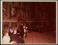 Vatican City. Unknown man addressing a group, with Pope Paul VI seated to the speaker's left