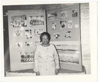 Gertrude Margaritte Ivory Bertram in front of display board