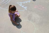 Young girl using chalk to draw a crab