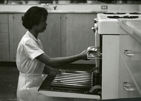 student placing grate in an oven