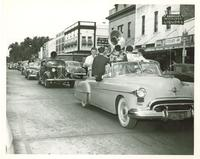 Several band members in a parade car