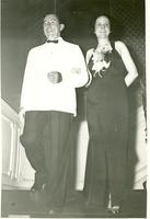 Claude and Mildred Pepper descending a staircase in formal clothes