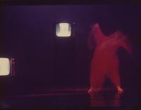 Dancer onstage with television sets