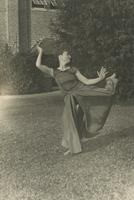 Costumed woman dances in grass