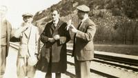 Paul Dirac standing with group next to train tracks