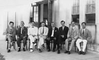 Paul Dirac and Werner Heisenberg sit with others on a porch