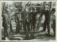 A group of men, including Claude Pepper, talking to a man in a hole