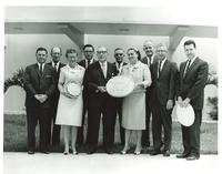 Claude Pepper posing with staff of Hialeah Junior High School and the Great Seal of the United States