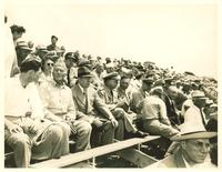 Claude Pepper and others sitting on a grandstand observing Infantry Day exercises at Fort Benning