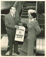 A stewardess pouring California Orange Juice into glass held by Claude Pepper