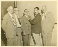 A group of men pinning a badge on Claude Pepper