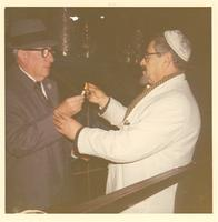 A man lighting a candle held by Claude Pepper