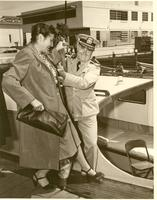 A man in uniform helping Mildred Pepper step onto boat