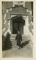 Mary Tarver Wearing Her Cap and Gown and Standing In Front of Gilchrist Hall