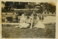 Four Women Sitting on the Ground in Front of the Fountain