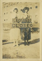 "Two Women Standing Behind ""Grounds Closed"" Sign"