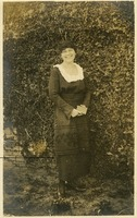 Unidentified Women Standing next to Ivy Covered Wall