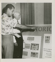 Two Unidentified Men Looking at Historic Bonds