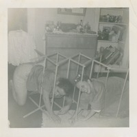 Two Women Crawling Through a Wooden Clothes Drying Rack