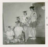 Pat Arrants with a Group of Women Wearing Caps While Clowning Around in a Dorm Hallway