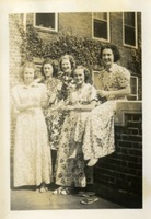 Five Women Sitting on Brick Wall Outdoors