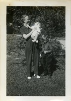 A Young Boy Standing next to a Woman Holding a Toddler
