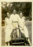 A Man and Two Women Posing with a Lawn Chair