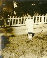 A Young Florence Standing near a Picket Fence