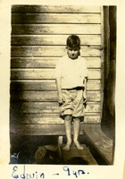 Young Boy Standing Near a House