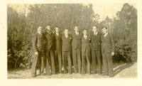 Eight Men Dressed in Suits Standing Outdoors