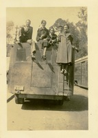 Five People Posed on Top of the Back of a Bus