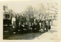 Large Group of Men and Women Standing and Crouching in Front of House