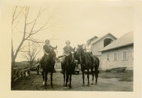 Three Women on Horses Outside of a Stable