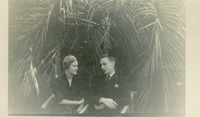 Man and Woman Sitting under Palm Trees