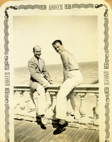 Two Men Sitting on Railing in Front of a Body of Water