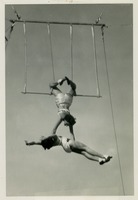 Two Circus Students Performing a Stunt on the Trapeze