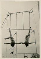 Two Circus Students Upside Down on a Trapeze