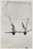 Two Circus Students Hanging Upside Down on a Trapeze