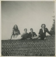 Four Students Next to Wall On Campus